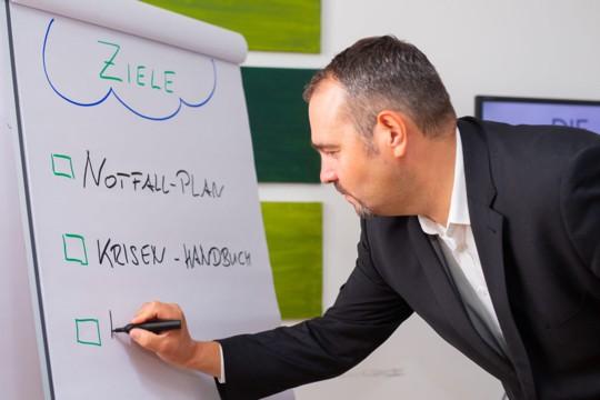 Markus Glanzer erläutert die Ziele des Notfall- und Krisenmanagements an einem Flipchart