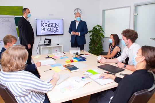 Die Krisenplaner Dieter Brückner und Markus Glanzer mit Teilnehmern eines Trainings im Bereich Notfall- und Krisenmanagement